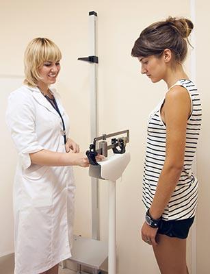 anorexie : docteur pesant une jeune patiente
