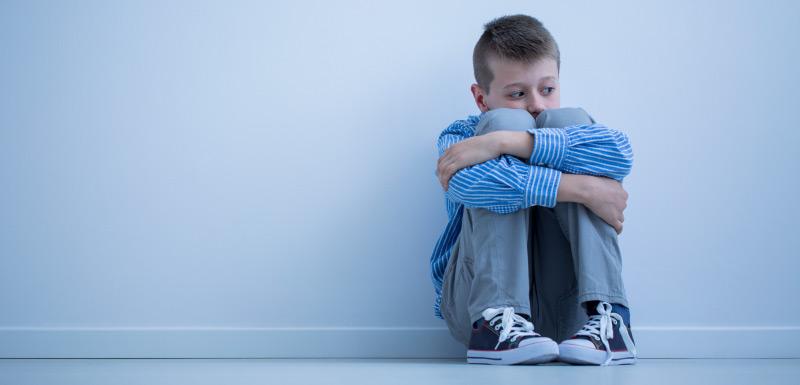 autistes : enfant assis la tête entre les genoux