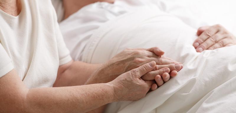 fin de vie, femme âgée tient la main d'un homme dans un lit d'hôpital