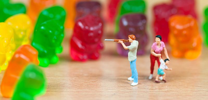 Aliments ultra-transformés, jouet figurine pointant son fusil sur des ours en gélatine pour protéger sa famille