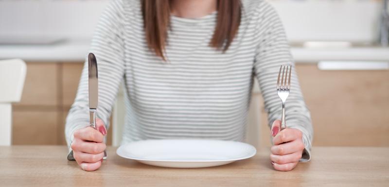régimes minceur femme devant une assiette vide