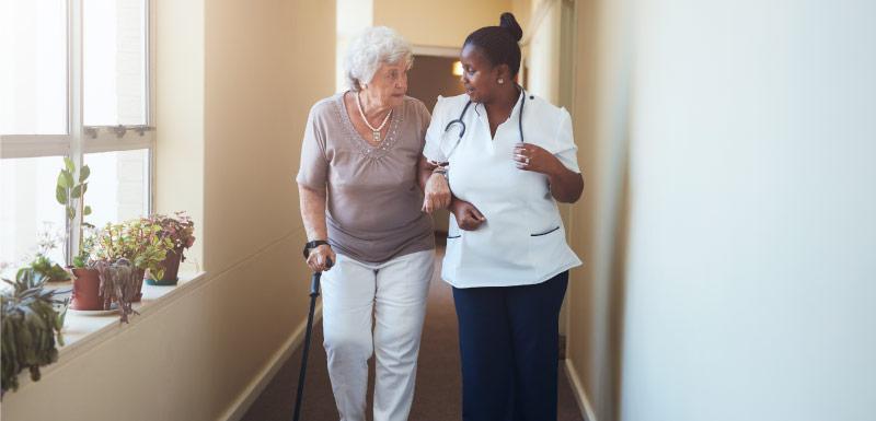 femme agée accompagnée par une infirmière vitesse de marche