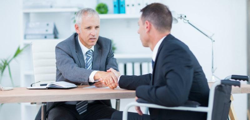 Deux hommes dans un bureau se serrant la main - Sclérose en plaques