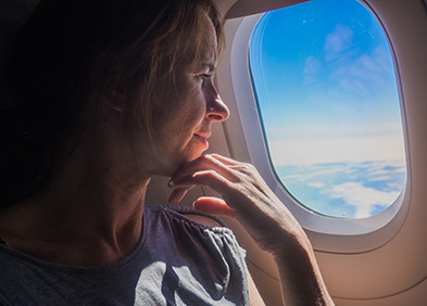 Femme regardant par le hublot d'un avion