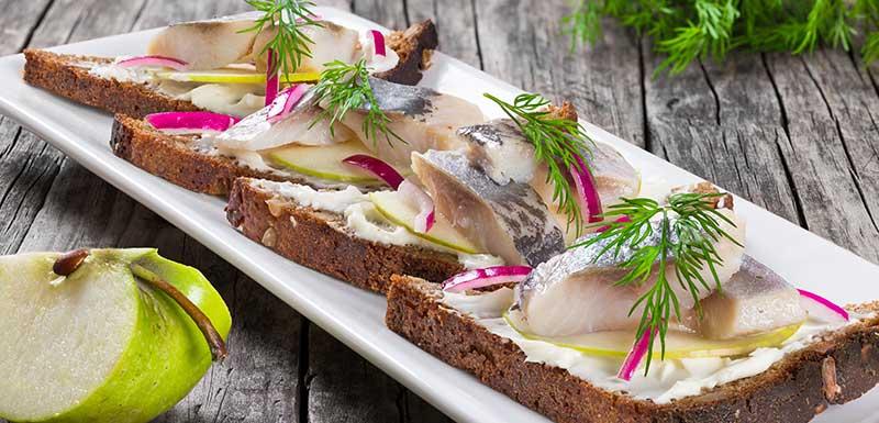 Sandwich avec filets de hareng, oignon, mariné au concombre et à l'aneth