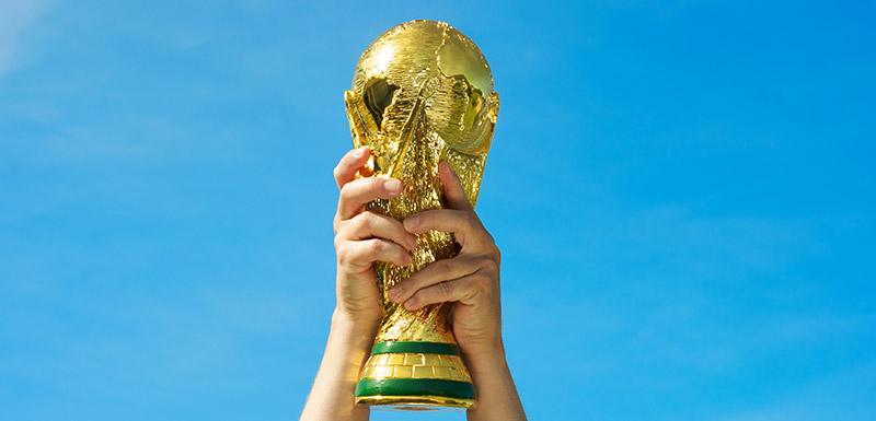 Deux mains brandissant le trophée de la coupe du monde de football