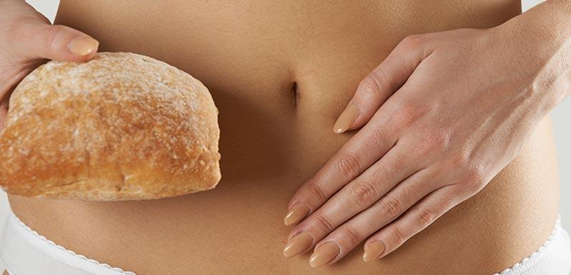 Femme dont une main est posée sur son ventre et dont l'autre main tient un pain