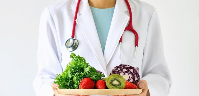 alimentation saine : un docteur tient une assiette de fruits et légumes frais