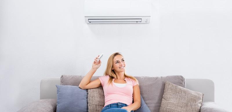 une femme profite de la climatisation tout en étant assise sur le canapé et règle le climatisseur avec la télécommande.
