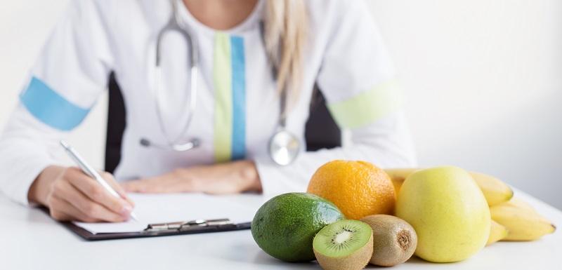 Une nutritionniste écrit la prescription destinée à un ealimentation saine sur un bureau avec des fruits