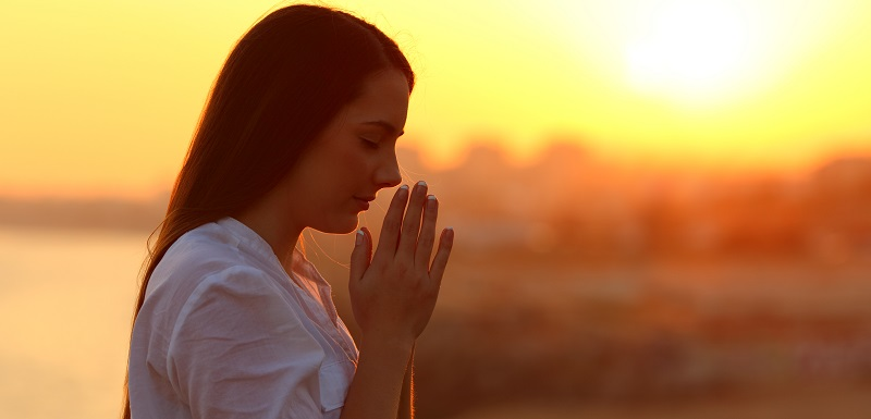 une femme est entrain de faire une prière.