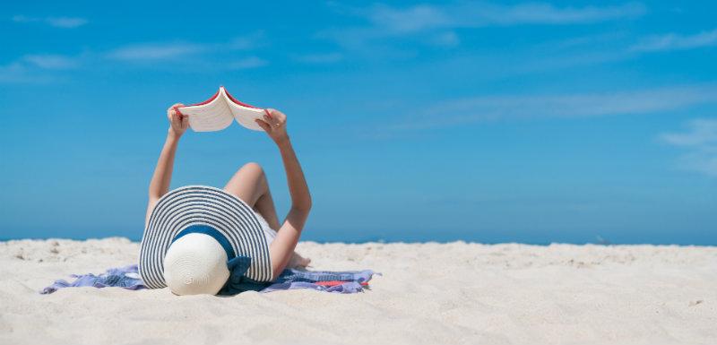 une femme est entrain de lire, allongée sur la plage