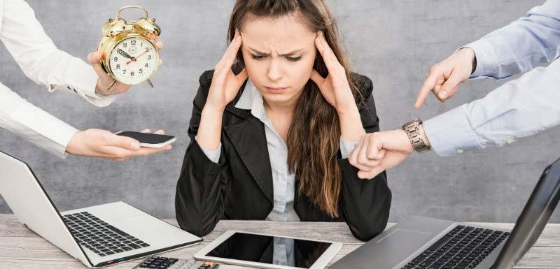Femme stressée devant plusieurs écrans