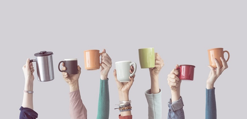 Plusieurs bras levés avec une tasse de café dans la main.