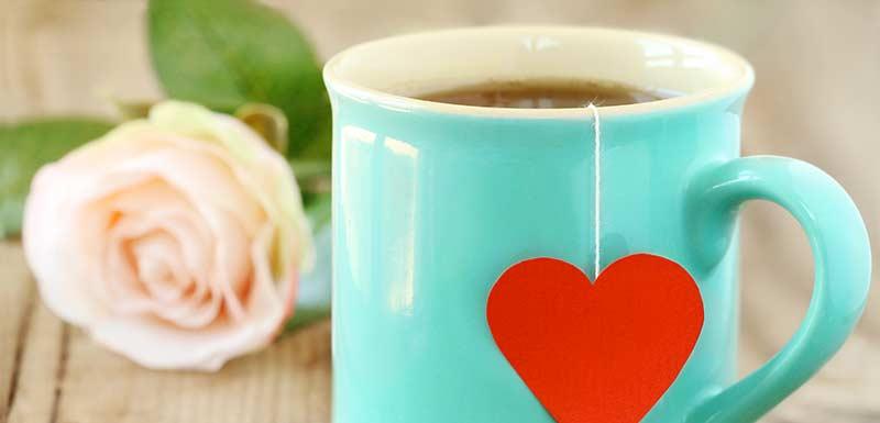 Une tasse avec un motif coeur contenant du thé vert