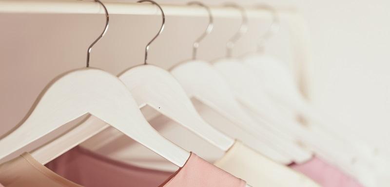 Vêtements sur des cintres rangés dans l'armoir