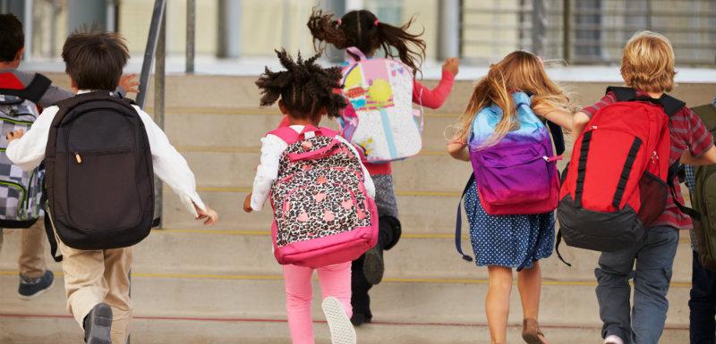 enfants qui courent avec leur cartable sur le dos