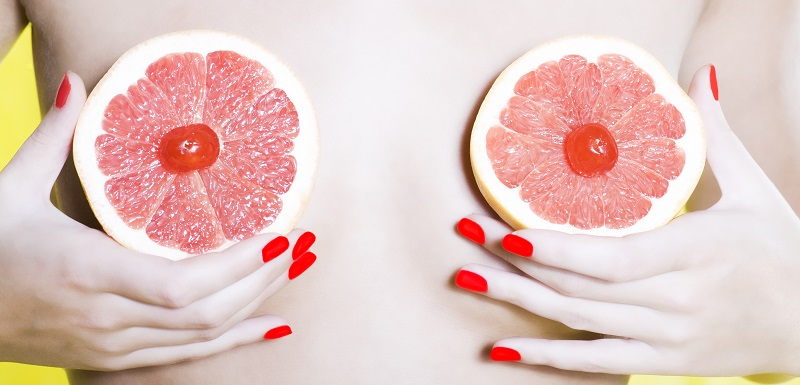 Une femme cache ses seins avec des fruits