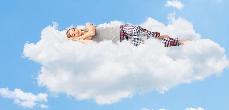 une femme entrain de s'endormir tranquillement sur le nuage