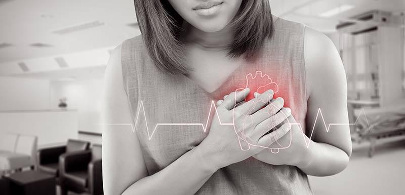 une femme se tient les mains sur le coeur, diclofénac risques cardiaques
