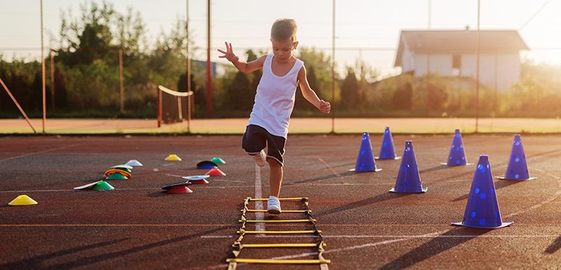 Petit garçon hyperactif sautant par-dessus des entraves dans un terrain d'entraînement