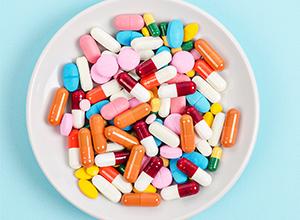 Assiette remplie de pilule colorées et des capsules médicales