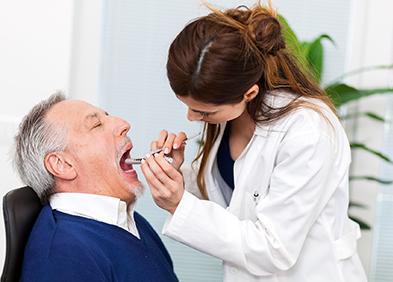 Médecin examinant l'intérieur de la bouche d'un patient