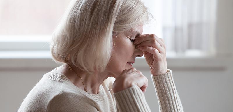 vielle femme fatiguée massant son nez