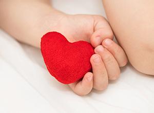 Bambin garde un cœur rouge en peluche à cause des cardiopathies congénitales