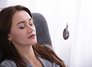 Femme étant hypnotisé avec un pendule pour diagnostic la dysmorphophobie