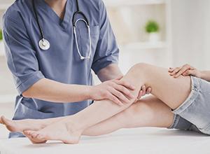 docteur massant la jambe d'un patient atteitn de la maladie de kennedy