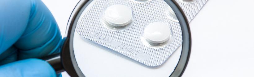 Loupe qui zoom sur une plaquette de médicament pour vérifier si c'est un placebov