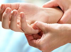 thérapeute manipulant une zone sensible d'un patient à cause des rhumatismes