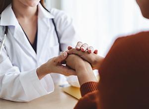 femme médecin massant la main d'une jeune femme à cause des rhumatismes