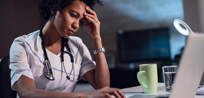 Médecin femme afro-américaine avec maux de tête travaillant la nuit sur son ordinateur portable
