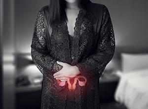 Femme en chemise de nuit en soie noir et robe de dentelle avec douleur utérus car bilan hormonal d'infertilité féminine
