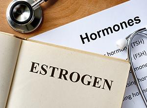 Estrogen écrit sur un livre avec une liste d'hormones pour un bilan hormonal d'infertilité féminine