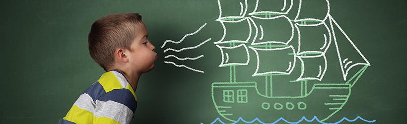 Enfant qui souffle un voilier à la craie pour vérifier la spirométrie