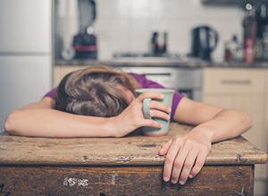 Femme fatigué à cause du stress et allongé sur la table de la cuisine avec une tasse de thé dans la main