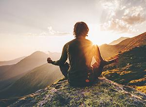 Homme faisant du yoga et de la médiation sur un flanc de montagne devant un coucher de soleil à cause du stress