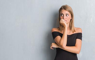 belle jeune femme élégante avec une robe grunge debout devant le mur gris qui est en stress car elle ronge ses ongles