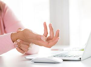 Femme tenant son poignet de douleur pendant qu'elle utilisait son ordinateur à cause de la tendinite