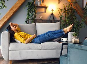 Jeune femme brunette détendant sur le divan après une longue journée pour soulager sa tendinite