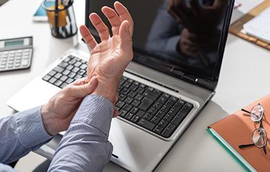 Homme d'affaires souffrant de douleurs au niveau du poignet à cause de la tendinite