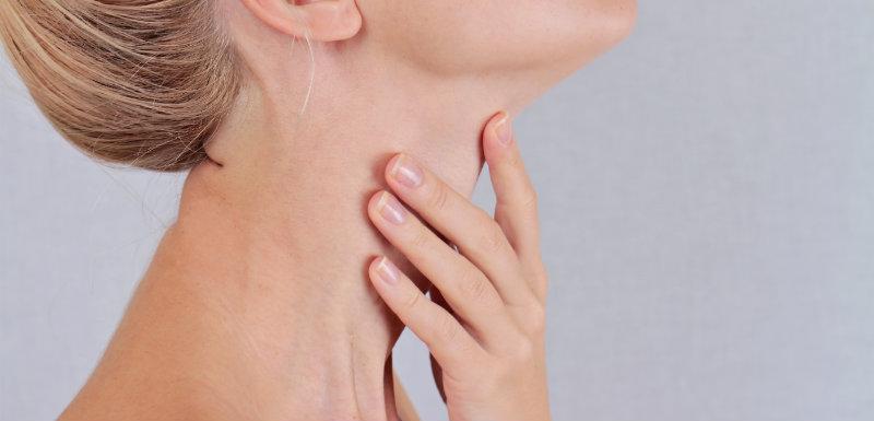 Femme controlant sa glande thyroïde pour la circonférence du cou