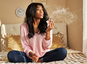 Femme afro-américaine fumant de la marijuana dans sa maison pour le leucoplasie