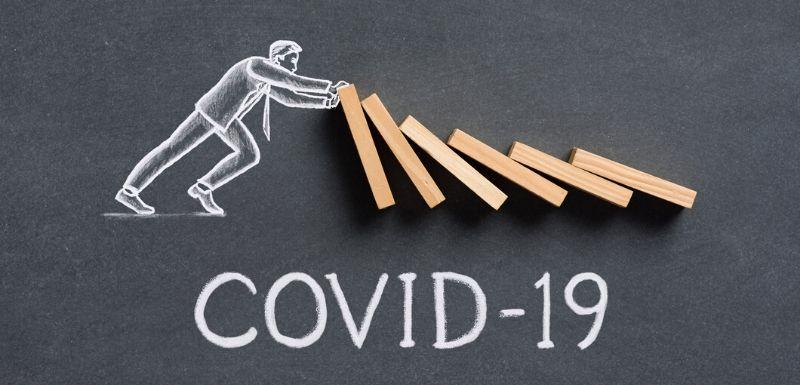 Bonhomme qui retient les dominos qui tombent les uns sur les autres, qui illustrent le virus covid-19