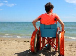Petit garçon en fauteuil roulant à la plage suite à une dystrophie musculaire