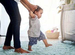 Enfant en short bleu et t-shirt gris essayant de faire ses premiers pas avec sa maman qui lui tient les mains.