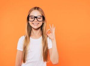 Jeune fille qui sourit avec ses lunettes sur le nez, devant un fond orange
